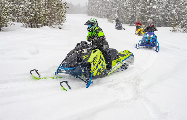 Photos of snowmobilers riding trail in snow