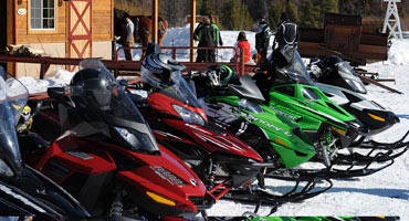 Various brands of snowmobiles parked against each other
